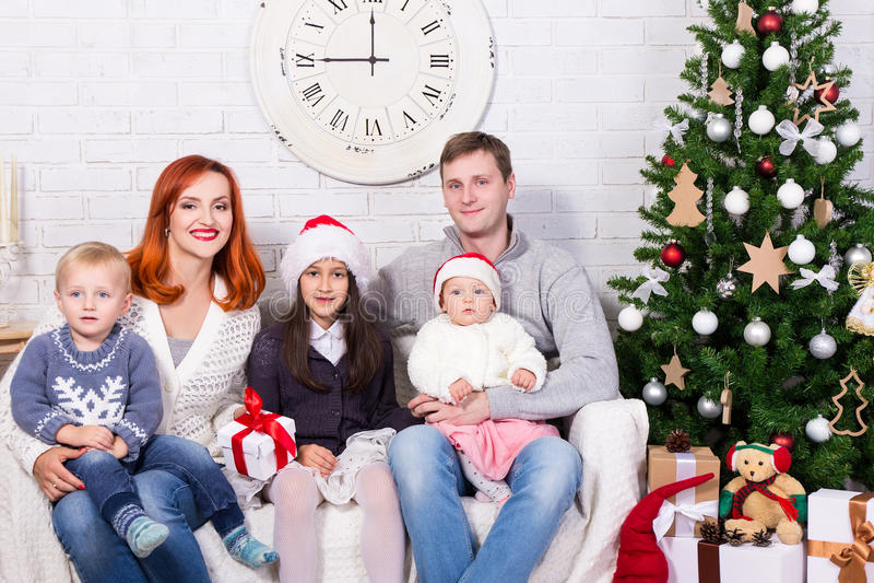 Jonge familie met giftdozen voor Kerstboom royalty-vrije stock fotografie