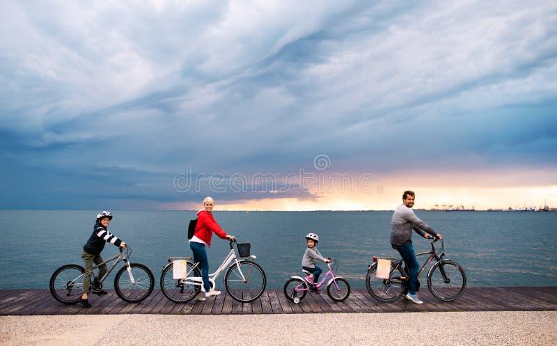 Jonge familie met kleine kinderen en fietsen in openlucht op strand royalty-vrije stock afbeeldingen