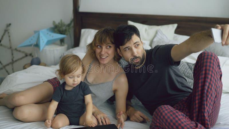 Jonge familie met leuk meisje die selfie portret op de zitting van de smartphonecamera in bed thuis nemen royalty-vrije stock afbeeldingen