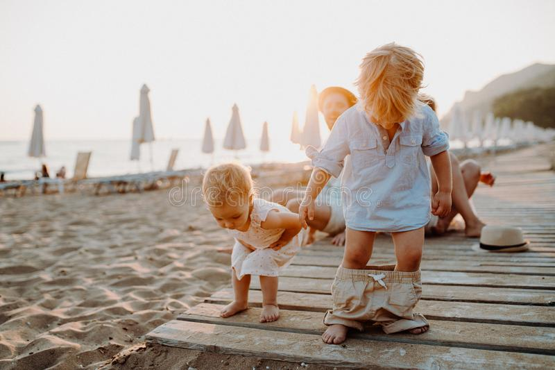 Jonge familie met peuterkinderen die pret op strand op de zomervakantie hebben royalty-vrije stock afbeeldingen