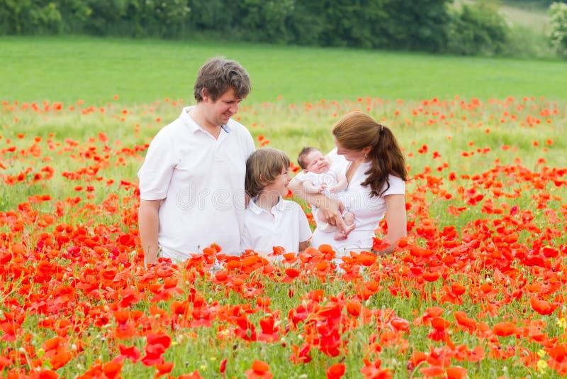 Jonge familie met twee jonge geitjes - zoon en pasgeboren dochter die - op het gebied van de papaverbloem stellen royalty-vrije stock foto's