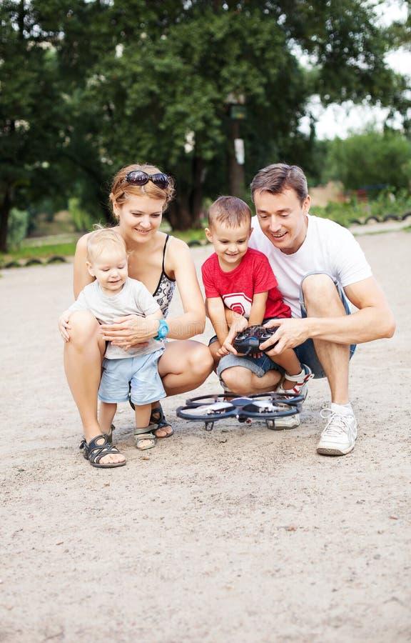 Jonge familie met twee jongens die met RC-stuk speelgoed spelen stock foto