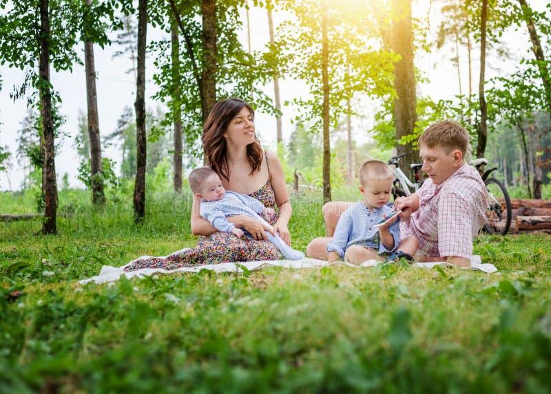 Jonge familie met twee jonge kinderen op een de zomerpicknick in p royalty-vrije stock afbeelding