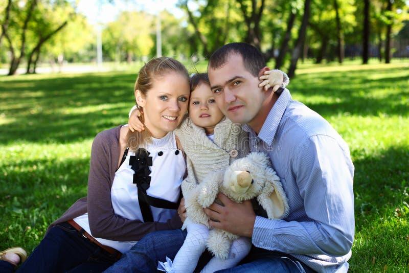 Jonge familie met weinig dochter in de zomerpark stock fotografie