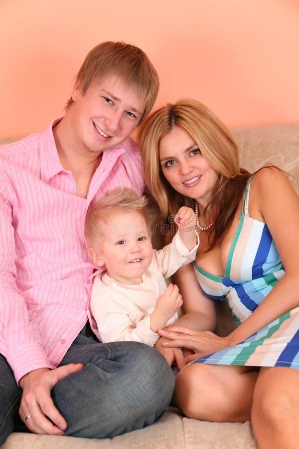 Jonge familie op bank in roze ruimte 3 royalty-vrije stock afbeelding