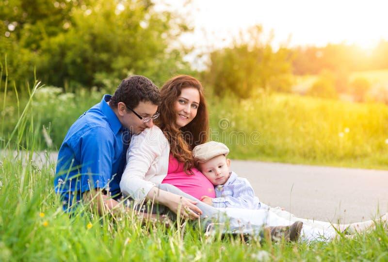 Jonge familie op een gang in groene zonnige de zomeraard stock foto