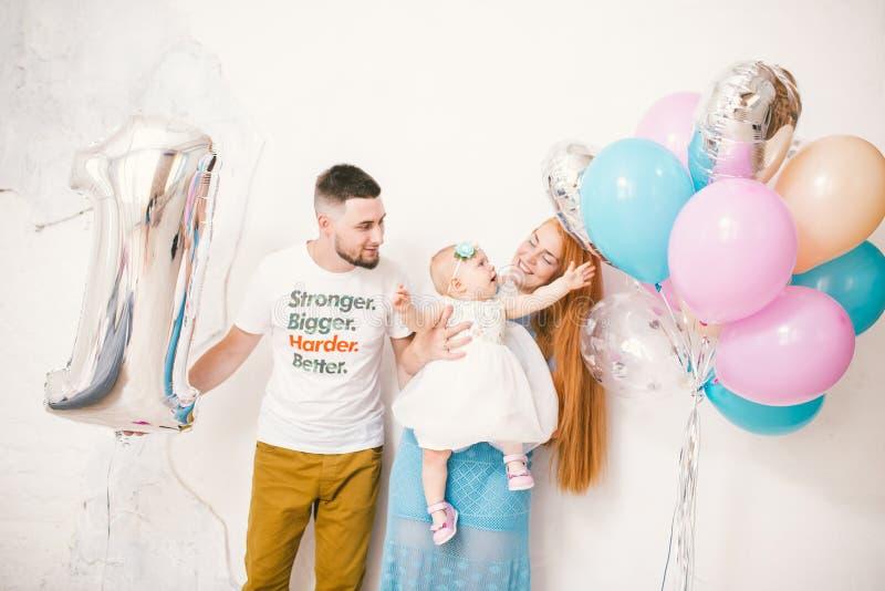 Jonge familie, oudersmamma en papa die een babymeisje één jaar op een witte achtergrond thuis houden Het concept een kinderen` s  stock foto's