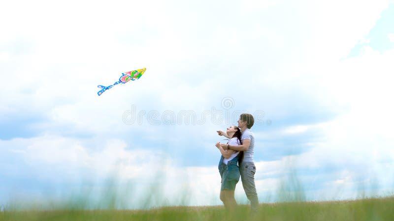 Jonge familie, paar die een vlieger in werking stellen tegen een blauwe hemel en wolken stock afbeelding