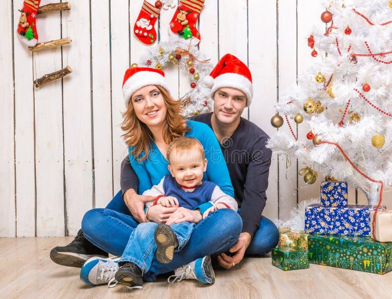 Jonge familie in rode hoeden met weinig zoon royalty-vrije stock afbeeldingen