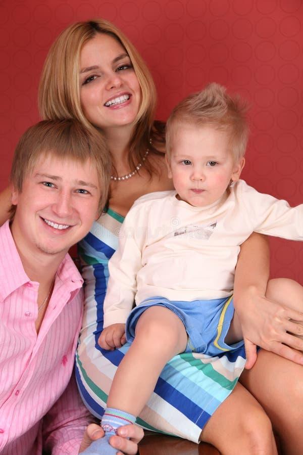 Jonge familie in rode ruimte stock foto's