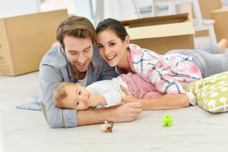 Jonge familie thuis met baby het liggen op de vloer royalty-vrije stock afbeelding
