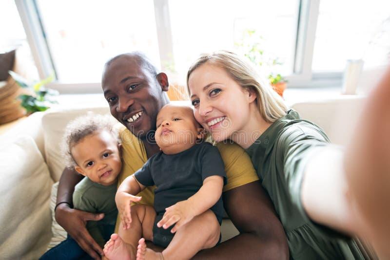 Jonge familie tussen verschillende rassen met kleine kinderen die selfie nemen stock afbeeldingen
