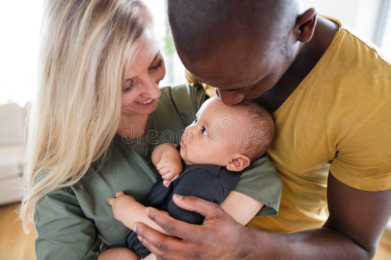 Jonge familie tussen verschillende rassen met weinig babyzoon thuis stock afbeeldingen