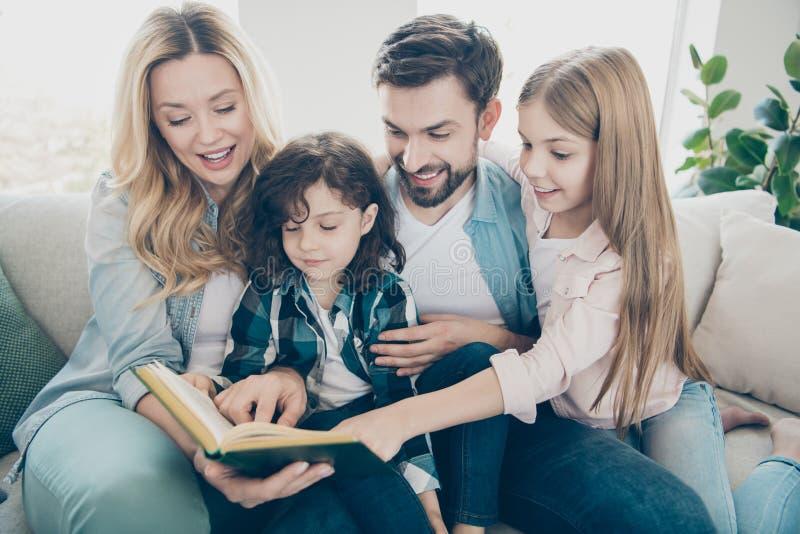 Jonge familie twee de goedgekeurde bank van de kinderen comfortabele zitting luistert de tekeningen van het het horlogesprookje v stock afbeelding