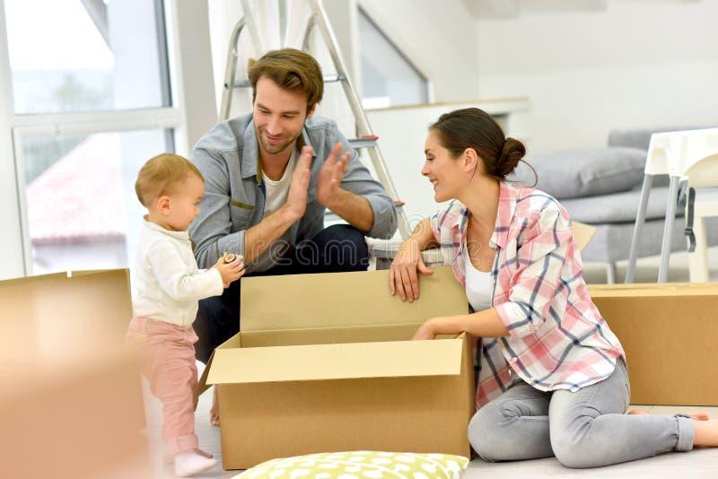 Jonge familie uitpakkende dozen stock foto