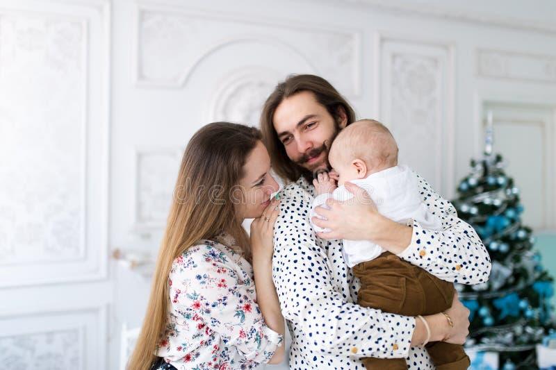 Jonge familie van drie die traditioneel Kerstavondwafeltje delen die zich tegen spar bevinden royalty-vrije stock fotografie