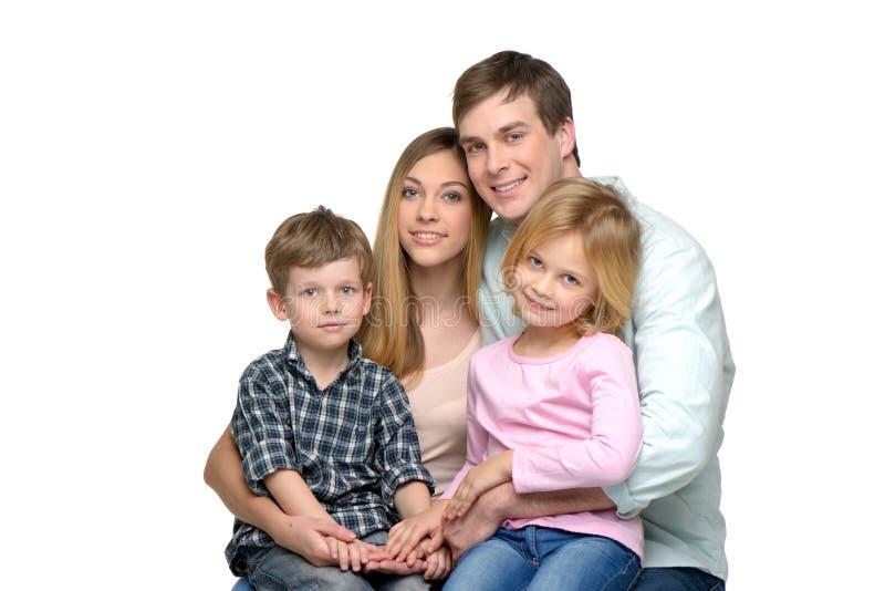 Jonge familie van vier die en camera stellen bekijken royalty-vrije stock foto's