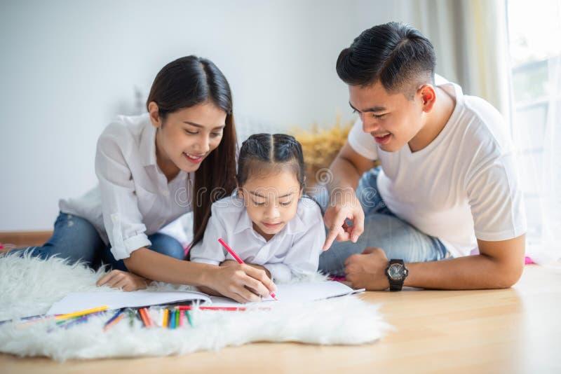 Jonge familietekening samen met kleurrijke potloden thuis stock afbeeldingen
