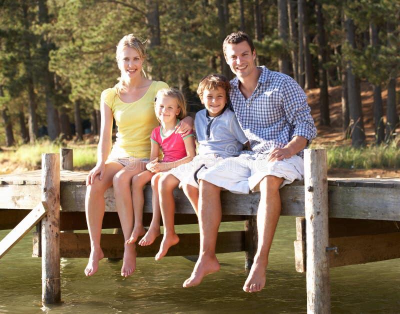 Jonge familiezitting door meer samen royalty-vrije stock afbeelding