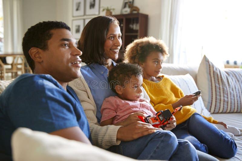 Jonge familiezitting samen op de bank in hun woonkamer die op TV, selectieve nadruk letten stock foto's