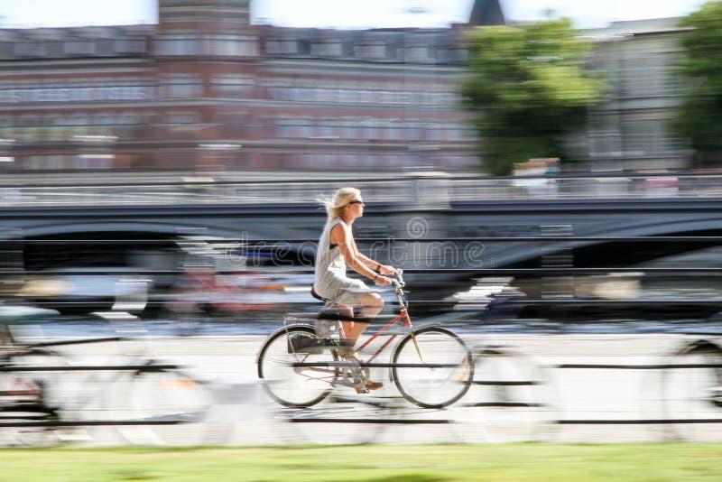 Jonge fietser die haar fiets dicht bij het stadscentrum berijden van Stockholm in een hete de zomerdag Beeld met opzettelijk moti stock foto
