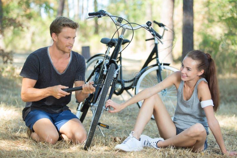Jonge fietsers die omhoog fietsband pompen royalty-vrije stock foto