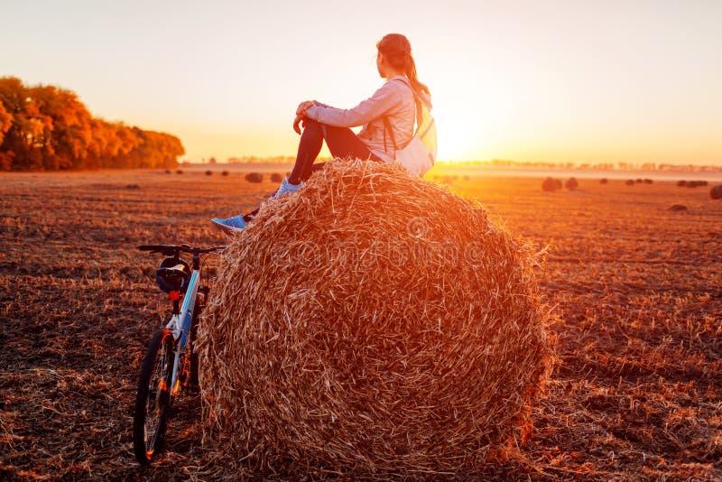 Jonge fietserzitting op hooiberg na een rit Vrouw die rust op de herfstgebied hebben Sportieve levensstijl stock fotografie