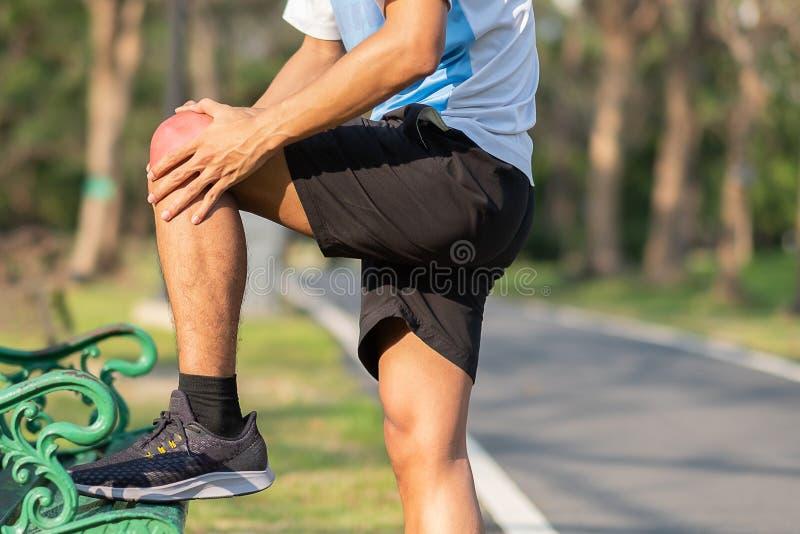 Jonge fitness mens die zijn verwonding van het sportenbeen houden spier pijnlijk tijdens opleiding Aziatische agent die kniepijn  royalty-vrije stock afbeelding