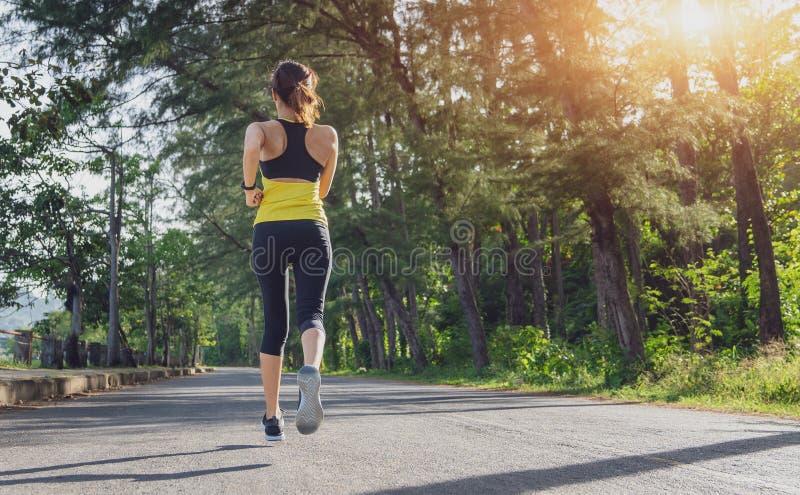 Jonge fitness sportvrouw die op de weg in de ochtend lopen, Jonge fitness sportvrouwagent die op tropische parksleep lopen Peo royalty-vrije stock foto's