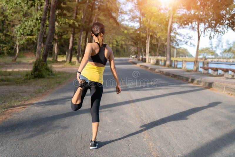Jonge fitness vrouwenagent het uitrekken zich benen vóór looppas op stad, Jonge fitness sportvrouw die op de weg in de ochtend lo stock afbeeldingen