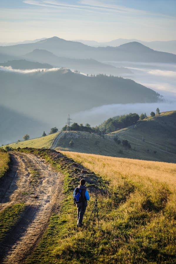 Jonge fotograaf in de bergen stock afbeelding