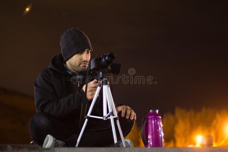 Jonge fotograaf die nachtfoto's nemen royalty-vrije stock afbeelding