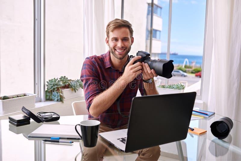 Jonge fotograaf die van zijn huisstudio werken royalty-vrije stock foto's
