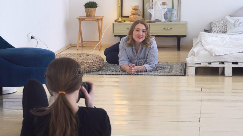 Jonge fotograaf in professionele studio die beelden die van het glimlachen model nemen op het tapijt liggen Professionele foto royalty-vrije stock foto's