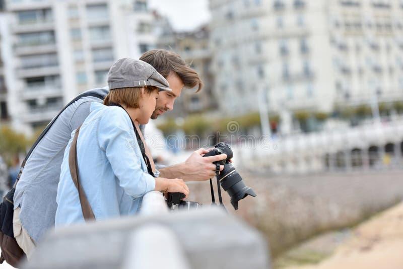 Jonge fotografen die fotoschoten controleren stock afbeelding