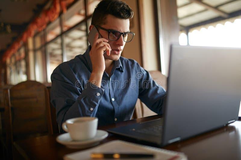 Jonge freelancer die met laptop werken en op cellphone met cliënt in bureau spreken Knappe Kaukasische zakenman binnen stock afbeelding