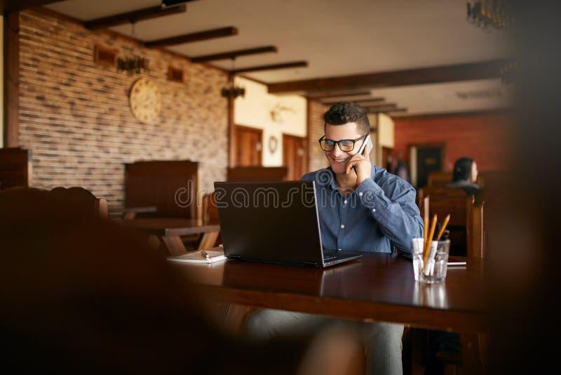 Jonge freelancer die met laptop werken en op cellphone met cliënt in koffie spreken Knappe Kaukasische zakenman binnen royalty-vrije stock fotografie