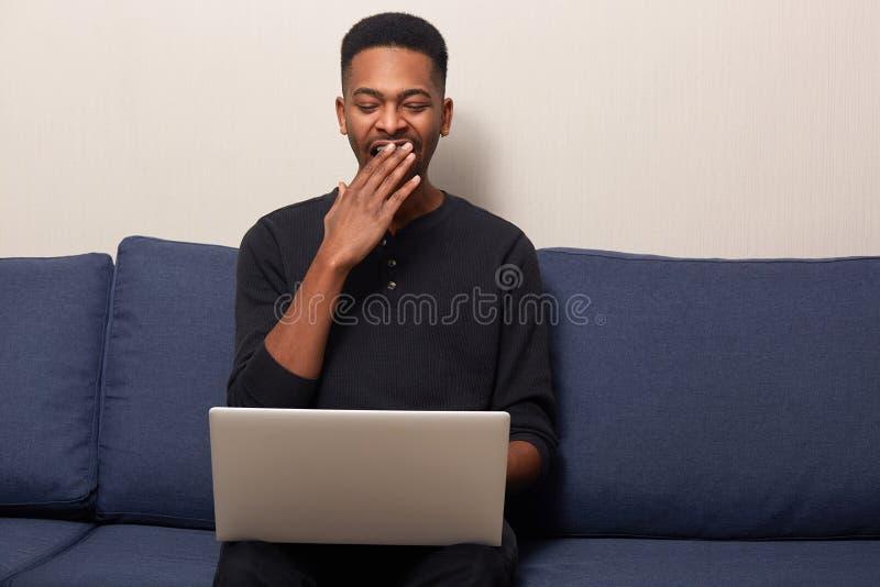 Jonge freelancer in op blauwe bank voor laptop zitten en vrijetijdskleding die, die kijkt vermoeid en uitgeput, hebbend partijen  royalty-vrije stock fotografie