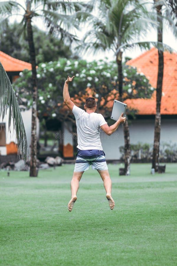 Jonge freelancermens die met laptop in het tropische park van het eiland van Bali springen royalty-vrije stock afbeelding