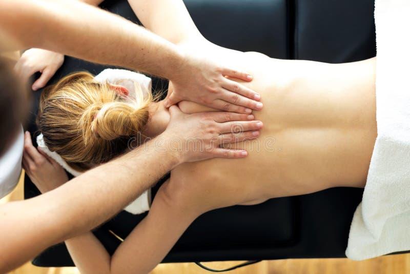 Jonge fysiotherapeut die een achterbehandeling doet aan de pati?nt in een fysiotherapieruimte stock afbeelding