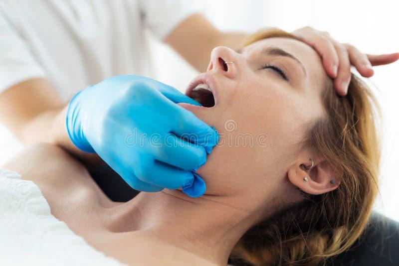Jonge fysiotherapeut die een gezichtsbehandeling doen aan de patiënt in een fysiotherapieruimte royalty-vrije stock fotografie
