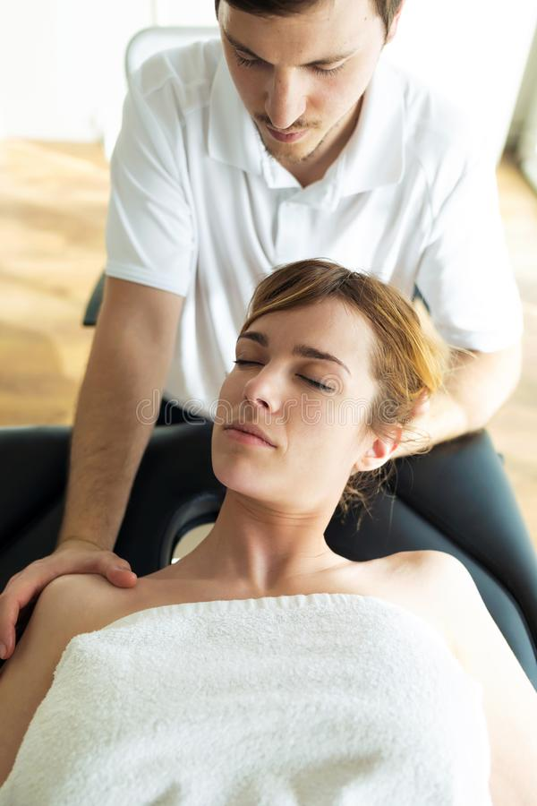 Jonge fysiotherapeut die een halsbehandeling doen aan de pati?nt in een fysiotherapieruimte stock foto's
