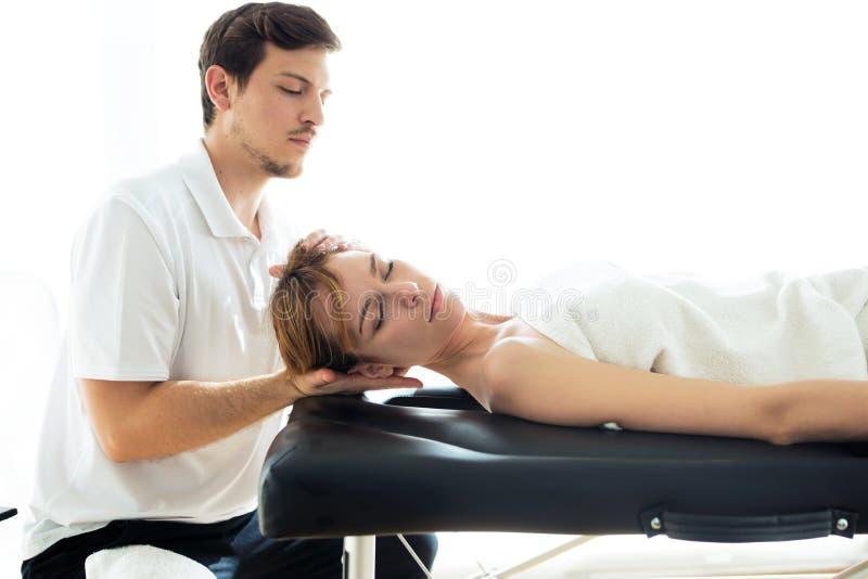 Jonge fysiotherapeut die een halsbehandeling doen aan de pati?nt in een fysiotherapieruimte royalty-vrije stock afbeelding