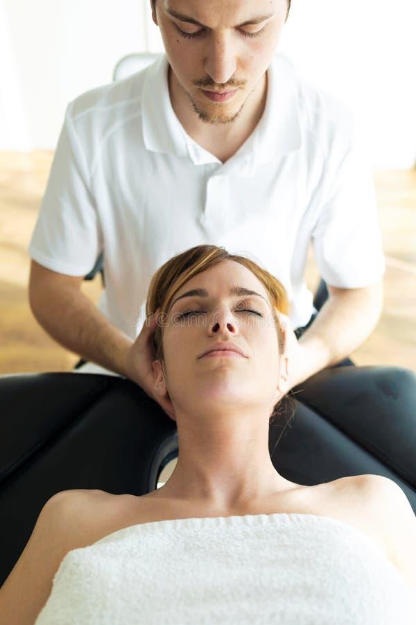 Jonge fysiotherapeut die een halsbehandeling doen aan de pati?nt in een fysiotherapieruimte stock foto