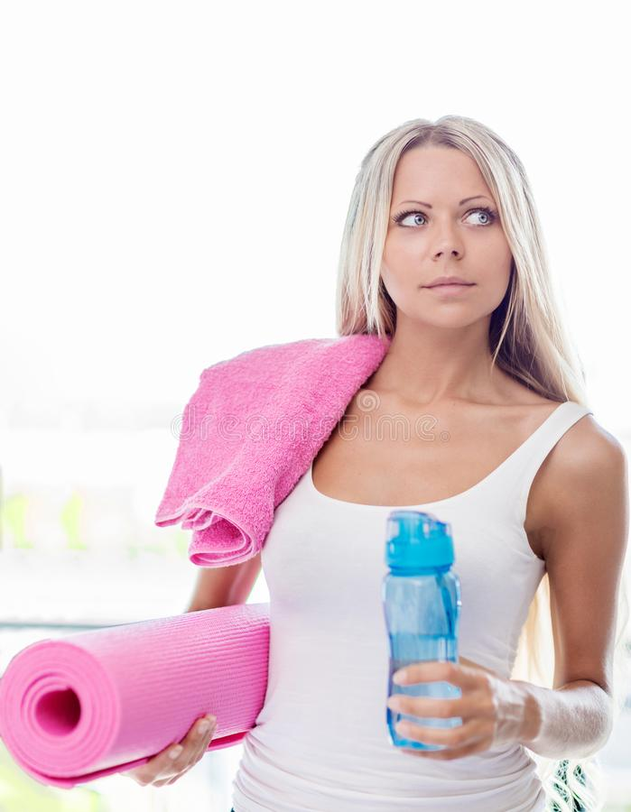 Jonge gaande de fitness van de blondevrouw sport met handdoek, fles wat royalty-vrije stock fotografie