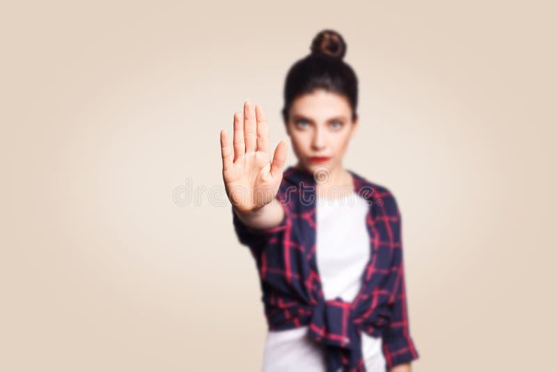 Jonge geërgerde vrouw met slechte houding die eindegebaar met haar palm uitgaand maken, zeggend nr, uitdrukkend ontkenning of bep stock afbeelding