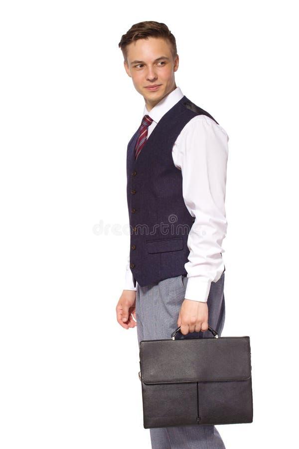 Jonge geïsoleerde zakenman - knappe mens die zich met aktentas bevinden stock foto
