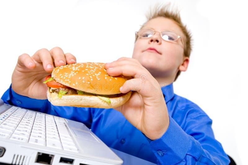 Jonge geïsoleerdee schooljongen met hamburger, stock afbeelding