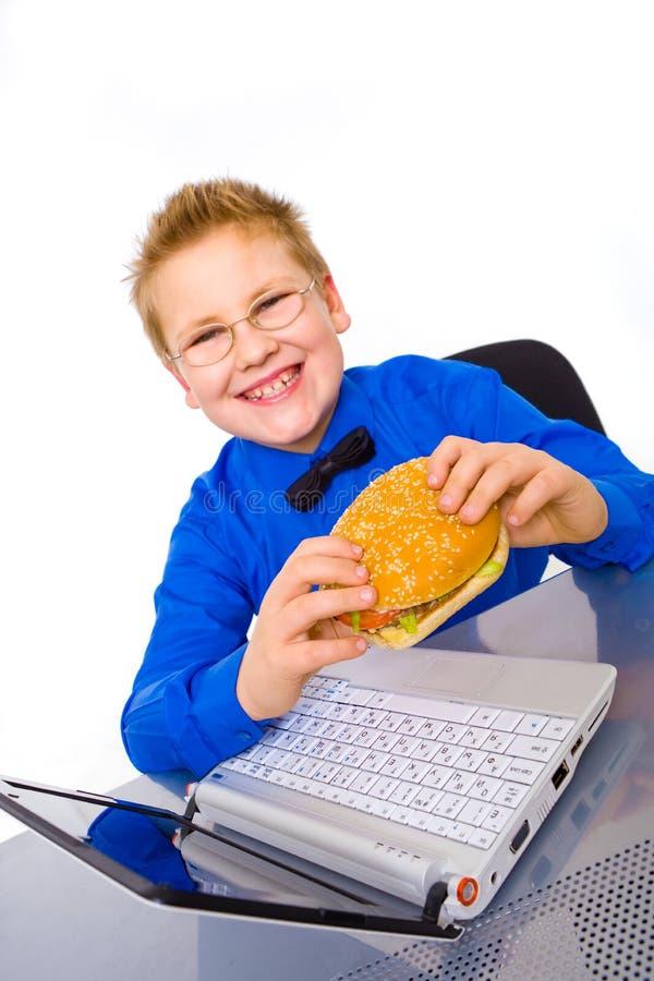 Jonge geïsoleerdeu schooljongen met hamburger, royalty-vrije stock afbeeldingen