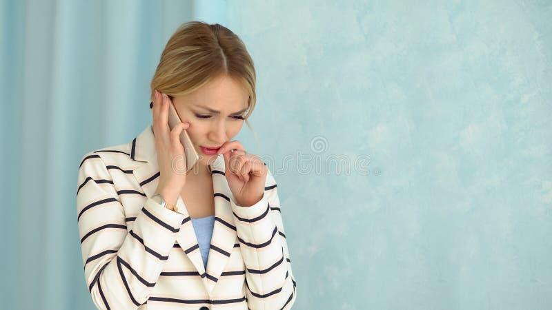 Jonge gealarmeerde vrouw in een gestreept jasje die op de telefoon spreken royalty-vrije stock afbeelding
